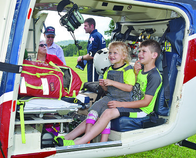 """The Taylor County Extension Office held a """"Family Farm Field Day"""" on Tuesday, and despite rainy weather, people showed up to the Doug Cox and Joe Wengerd Farms for an evening of """"fun, fellowship and education.""""  Above, Olivia Jones (left), 3, and Isaac Jones, 8, both of Loretto, check out the inside of an Air Evac helicopter."""