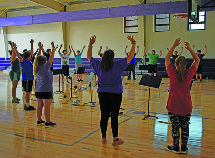 Band members at CHS stretch up high as they breathe deeply, an exercise meant to help expand lung capacity.