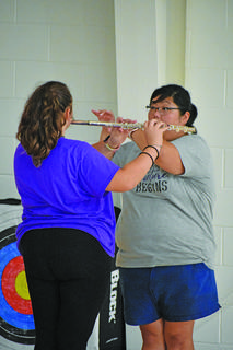 Brittany Johnson, assistant band director, shows CHS freshman Kadence Houk the proper, powerful stance for holding a flute.