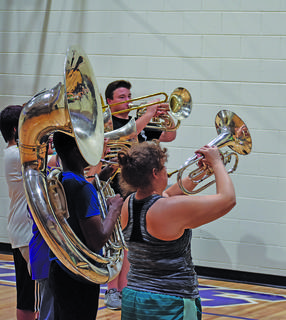 A group of CHS brass players practice holding their elbows outward when lifting their instruments. This posture allows players to appear larger, and more powerful on the field.