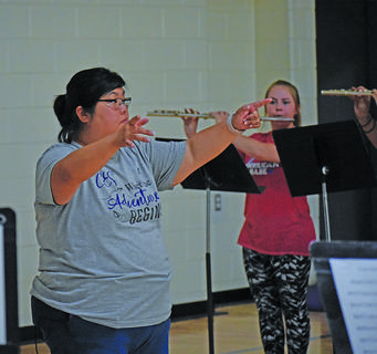Brittany Johnson, CHS assistant band director, conducts students as they play their first notes of the season.