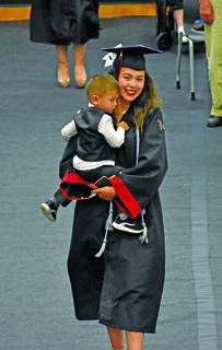 Taylor County graduate Emily Chea walks to her seat with her son during Friday's graduation ceremony at Citizens Bank Arena.