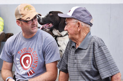 Taylor County PVA Chad Shively, left, and former Campbellsville Mayor Paul Osborne enjoy conversation on Main Street Saturday afternoon, as Shively's dog Finn looks on.