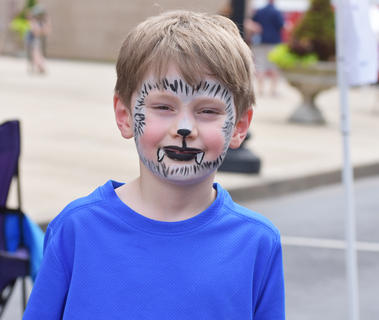 Sawyer Essex, 6, from Marion County, shows off his face paint on Saturday afternoon at Folk Fest.