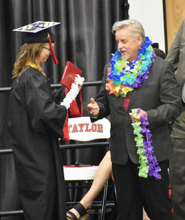 TCHS Senior Spencer Agee places leis on Superintendent Roger Cook to commemorate Cook's upcoming retirement.