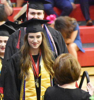 TCHS Senior Lexi Raikes walks across the stage at graduation.
