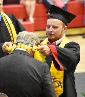 TCHS Senior Seth Wise places leis on Superintendent Roger Cook to commemorate Cook's upcoming retirement.