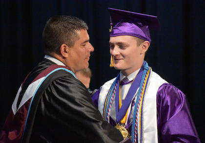 CHS Senior and Class Valedictorian Bryce Richardson shakes hands with CIS Superintendent Kirby Smith.