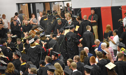 TCHS graduates spray silly string in celebration following graduation at TCHS.