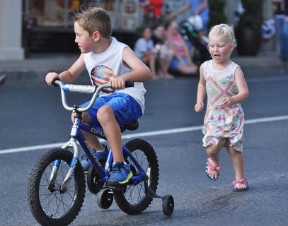 Lia Graham, right, chases her cousin Kyler Gaines during downtown festivities Tuesday night.