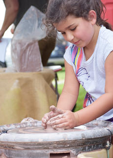 Blaire Arnold, 6, of Bowling Green, practices her hand at clay pottery at the Fall Heritage Festival at the Homeplace on Green River.