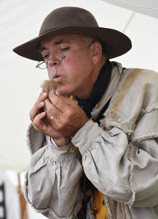 Ken Hill, a colonial era re-enactor from Columbia, demonstrates flint and steel firemaking techniques from that time period.