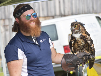 A worker with the Liberty Nature Center in Somerset holds an owl at their exhibit at the Homeplace on Green River.