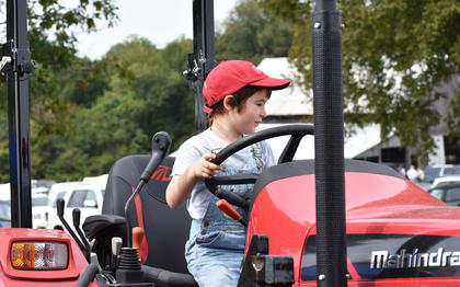 William Bela, from Hill and Hollow Farm in Edmonton, climbs aboard a tractor at the Fall Heritage Festival.