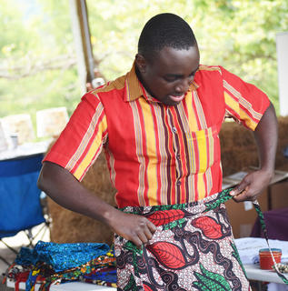 Derrick Kisita, from Uganda, demonstrates how to wear a Ugandan garment. Kisita sold multiple items from Uganda through Uganda Counseling and Support Services (UCSS).