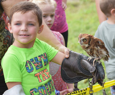 Blayden Wheeler, 5, from Atlanta, Georgia, holds an owl from the Liberty Nature Center exhibit.