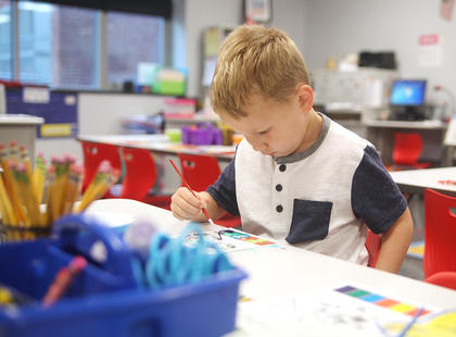 Carter Hines, 5, paints a picture before his kindergarten classmates arrive on the first day of school at Taylor County Elementary School.