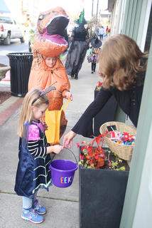 Alayna Willis, 5, gets her candy during trick-or-treat on Main Street Monday, while Brayden Willis, 8, waits his turn.