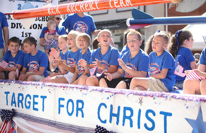 Members of the Kentucky Christian Academy archery team ride on a float during Friday morning's Fourth of July parade in downtown Campbellsville. The KCA archery team won a national championship earlier this year.