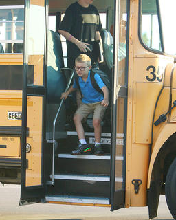 Students are ready to make the leap into a new school year as they exit the bus on the first day of classes.