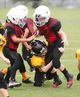 Bentley Chewning runs the ball for Taylor County Red youth football team Saturday in Washington County.