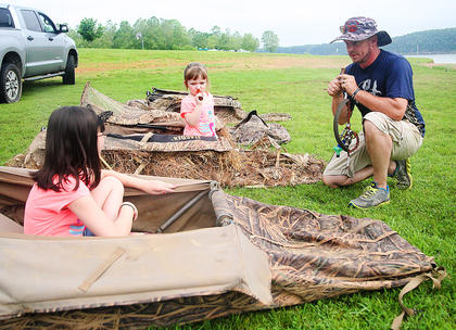 Todd Sharp with Green River Gobblers teaches 10-year-old Andrea Scott, left, and her sister, Emily, 6, how to use a duck call at the Kids Outdoor Day at Green River Lake State Park.