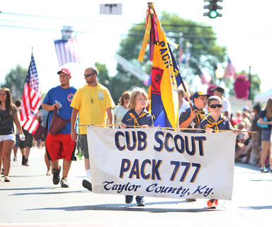 Taylor County Cub Scout Pack 777 members march with their banner during Friday's parade.