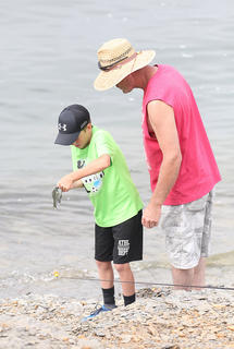 Layton Froggett, 10, gets a little help from his dad, Michael, with a fish he caught at the Kids Outdoor Day at Green River Lake State Park.