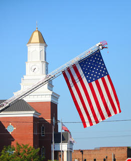 A giant American flag hangs in front of the Taylor County Justice Center early on the morning of the Fourth of July.