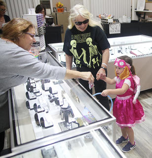 Abigail Keltner, 4, gets a Halloween treat from Patti Phillips at Tucker Diamonds and Gold Monday.
