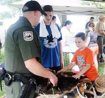 Drayden Clifton, 8, of Campbellsville, feels a beaver pelt, displayed by officer Jared Ervin with the Kentucky Department of Fish and Wildlife at Satudray's Kids Outdoor Day at Green River Lake State Park.