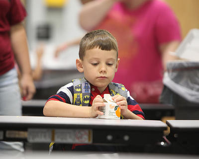 Lyndon Mascoe, 6, works to open his orange juice at breakfast before heading to his first-grade class at Taylor County Primary Center.
