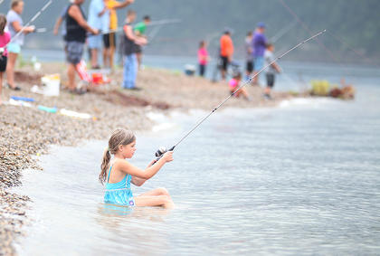 Madison Burton, 7, of Cox's Creek, takes a seat in the water as she fishes in Saturday's Kids Fishing Derby at Green River Lake State Park.
