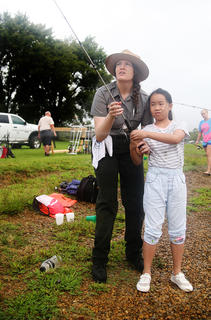 Green River Lake State Park Ranger Angel Iverson helps 10-year-old Sunny Zhauo with her fishing pole. Sunny and her family recently came to Campbellsville from China.