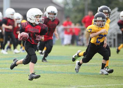 Aden Coslow runs the ball for Taylor County Red youth football team Saturday in Washington County.