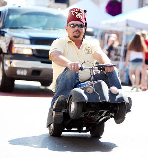 A member of the Mark Twain Shrine Club of Columbia performs a wheelie on his miniature car during the Fourth of July parade Friday.