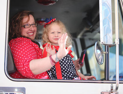 Dressed in her red, white and blue, a young girl waves to the crowd from the cab of a fire engine.