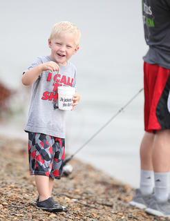 Asher Hines, 3, finds the perfect worm to use for bait during Saturday's Kids' Fishing Derby.