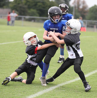 Brynden Perkins, left, and Jacob Marcum work to bring down a Washington County runner in Saturday's youth league football action.