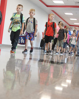 Students make their way from the gym to their classrooms on the first day of school.