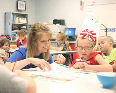 Taylor County kindgergarten teacher Chanci Patterson helps Rhyalynn Johnson, 4, with a painting on the first day of school.