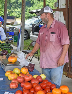 Jacky Pierce, of Brush Creek Blueberries on Taylors Chapel Road in Campbellsville, weighs one of his larger tomatoes as he watches patrons browse the farmers' market.