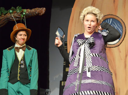 Aunt Sponge, portayed by Ellie Hite, sings as Grasshopper, played by Andy O'Daniel, listens.