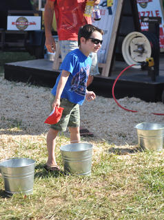 "James Thompson tries his hand at ""Feed the Animals,"" a variation of cornhole, at the Taylor County Fair on Wednesday night."
