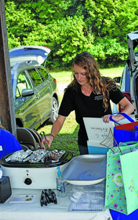 Kara Back, horticulture agent at the Taylor County Extension Office, refills a crockpot keeping steak and pepper skewer samples warm.