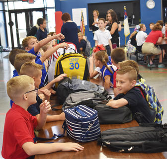 KCA students gather at a table in the cafeteria before the start of school Wednesday morning.