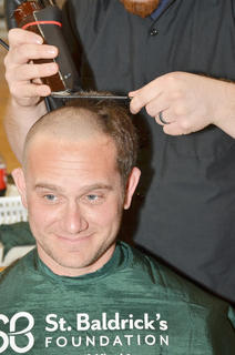 Keith Bricken smiles as his head is shaved.