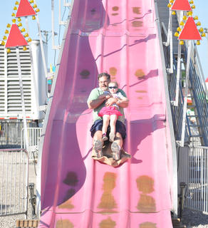 Brian Kester completes the Fun Slide with his daughter, Allyssa, on Wednesday at the Taylor County Fair.