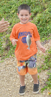 Alex Brewer, 5, of Buffalo, smiles as he looks at a fish caught Saturday morning.