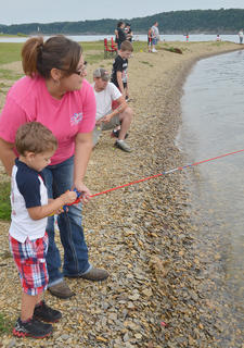 Rose Morgan of Greensburg helps her son, Connor, 3, cast his line.